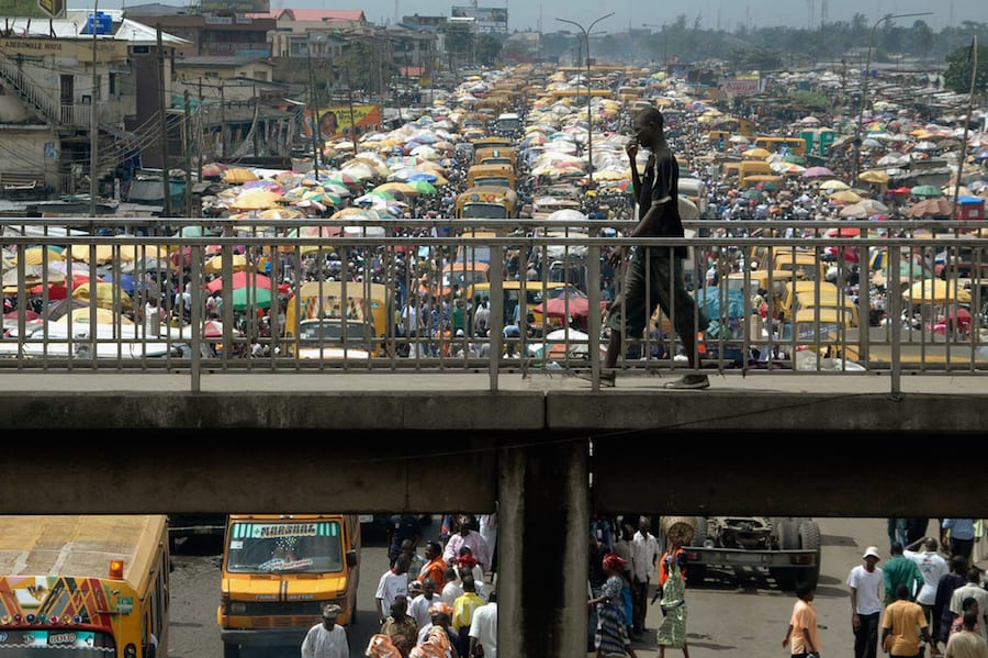 A man walks on a pedestrian bridge overlooking traffic in Lagos, Nigeria, September 18, 2006. The Africities 4 summit aimed at tackling the problems of the continent's expanding cities and huge slums opened on Monday in Nairobi. REUTERS/Akintunde Akinleye (NIGERIA) - RTR1HGS1